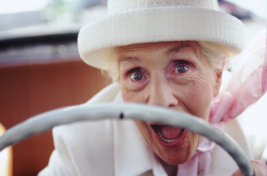 Ecstatic senior woman driving a convertible